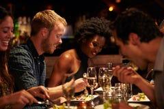 Groupe d'amis appréciant le repas dans le restaurant Photo libre de droits