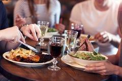 Groupe d'amis appréciant le repas dans le restaurant Image stock