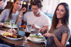 Groupe d'amis appréciant le repas dans le restaurant Images stock