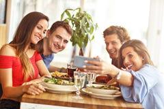 Groupe d'amis appréciant le repas dans le restaurant Photographie stock