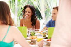 Groupe d'amis appréciant le repas dehors à la maison Image libre de droits