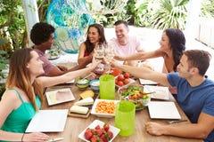 Groupe d'amis appréciant le repas dehors à la maison Photo libre de droits