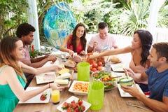 Groupe d'amis appréciant le repas dehors à la maison Photo stock