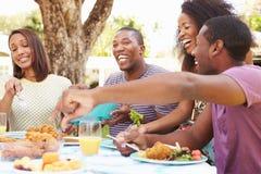 Groupe d'amis appréciant le repas extérieur à la maison Photographie stock libre de droits