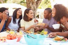Groupe d'amis appréciant le repas extérieur à la maison Image stock