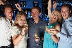 Groupe d'amis appréciant le verre de Champagne In Bar Photographie stock libre de droits
