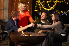 Groupe d'amis appréciant même des boissons par Firepit Images libres de droits