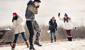 Groupe d'amis appréciant un combat de boule de neige dans la neige en hiver Images libres de droits