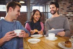 Groupe d'amis appréciant un dessert avec le comprimé Image libre de droits