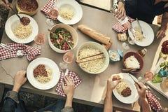Groupe d'amis appréciant un repas ensemble dehors Photographie stock libre de droits