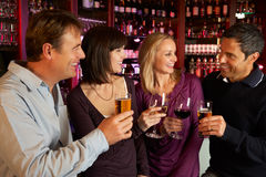 Groupe d'amis appréciant la boisson ensemble dans le bar Photographie stock