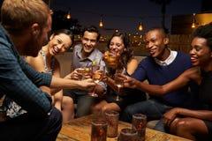 Groupe d'amis appréciant la nuit à la barre de dessus de toit Image stock