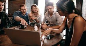 Groupe d'amis au café et de regarder l'ordinateur portable Photos libres de droits