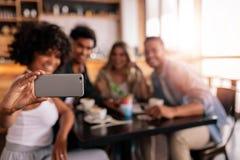 Groupe d'amis au café prenant le selfie Images libres de droits