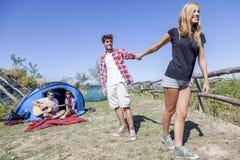 Groupe d'amis au terrain de camping tout en détendant Images libres de droits