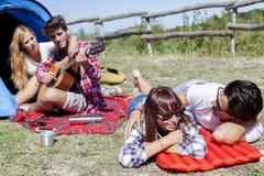 Groupe d'amis au terrain de camping tout en détendant Photos libres de droits