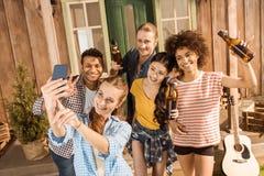 Groupe d'amis avec de la bière ayant l'amusement et prenant le selfie Images libres de droits