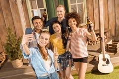 Groupe d'amis avec de la bière ayant l'amusement et prenant le selfie sur le smartphone Image stock