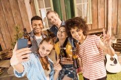 Groupe d'amis avec de la bière montrant le signe de paix et prenant le selfie Images stock