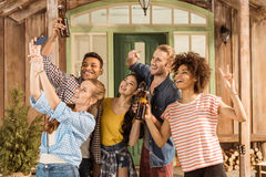 Groupe d'amis avec de la bière montrant le signe de paix et prenant le selfie Photos stock