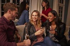 Groupe d'amis avec des boissons appréciant la partie de Chambre ensemble Images stock