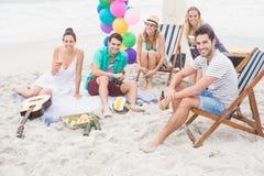 Groupe d'amis avec des boissons ayant l'amusement ensemble sur la plage Photos libres de droits