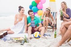 Groupe d'amis avec des boissons ayant l'amusement ensemble sur la plage Images libres de droits