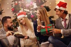 Groupe d'amis avec des cadeaux de Noël à la maison Images libres de droits