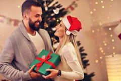 Groupe d'amis avec des cadeaux de Noël à la maison Image stock