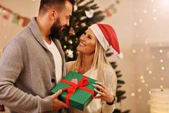 Groupe d'amis avec des cadeaux de Noël à la maison Photos stock
