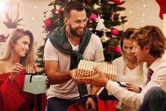 Groupe d'amis avec des cadeaux de Noël à la maison Images stock