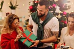 Groupe d'amis avec des cadeaux de Noël à la maison Photo libre de droits