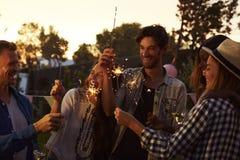 Groupe d'amis avec des cierges magiques appréciant la partie extérieure Photo libre de droits