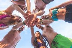 Groupe d'amis avec des mains sur la pile au bord de la mer Photo stock