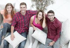 Groupe d'amis avec des oreillers, s'asseyant sur le divan Photo stock