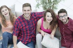 Groupe d'amis avec des oreillers, s'asseyant sur le divan Image stock