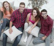 Groupe d'amis avec des oreillers, s'asseyant sur le divan Photographie stock libre de droits