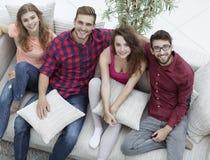 Groupe d'amis avec des oreillers, s'asseyant sur le divan Images libres de droits