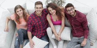 Groupe d'amis avec des oreillers, s'asseyant sur le divan Photos libres de droits