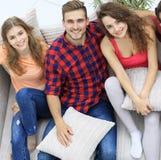 Groupe d'amis avec des oreillers, s'asseyant sur le divan Photo libre de droits