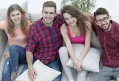 Groupe d'amis avec des oreillers, s'asseyant sur le divan Photos stock