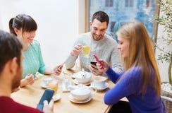 Groupe d'amis avec des smartphones se réunissant au café Images libres de droits