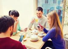 Groupe d'amis avec des smartphones se réunissant au café Images stock
