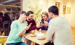 Groupe d'amis avec des smartphones se réunissant au café Image libre de droits
