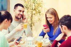 Groupe d'amis avec des smartphones se réunissant au café Image stock