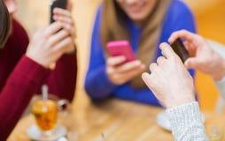 Groupe d'amis avec des smartphones se réunissant au café Photos stock
