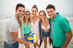 Groupe d'amis avec du ballon de plage ayant l'amusement sur la plage Photos stock