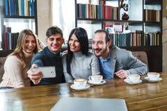 Groupe d'amis avec du café et de regarder le smartphone Images stock