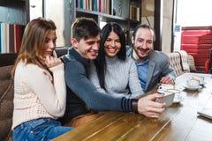Groupe d'amis avec du café et de regarder le smartphone Photos stock