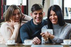 Groupe d'amis avec du café et de regarder le smartphone Image stock